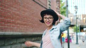 Портрет милого брюнета идя outdoors поворачивать к камере указывая усмехаться акции видеоматериалы