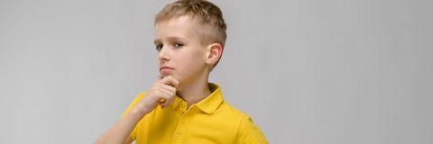 Портрет милого маленького белокурого кавказского мальчика в желтое неуверенном футболки озадаченного на серой предпосылке стоковое изображение rf