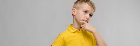 Портрет милого маленького белокурого кавказского мальчика в желтое неуверенном футболки озадаченного на серой предпосылке стоковое фото