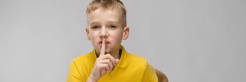 Портрет милого маленького белокурого кавказского мальчика в желтой футболке показывая shh знак на серой предпосылке стоковая фотография