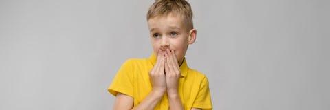 Портрет милого маленького белокурого кавказского мальчика в желтой вспугнутой футболке озадаченной удивленный на серой предпосылк стоковые изображения rf