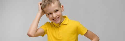 Портрет милого маленького белокурого кавказского мальчика в желтой футболке думая на серой предпосылке стоковая фотография