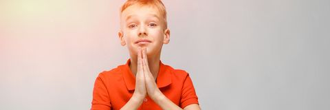 Портрет милого маленького белокурого кавказского мальчика в оранжевой футболке надеясь на серой предпосылке стоковые изображения rf