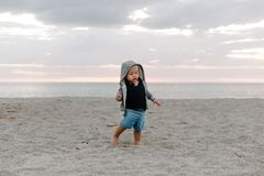 Портрет милого маленького ребенка ребенка играя и исследуя в песке на пляже во время снаружи захода солнца на каникулах в Hoodie стоковые фото