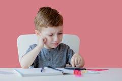 Портрет милого мальчика ребенк дома делая домашнюю работу Немногое сконцентрированный ребенок писать с красочным карандашем, внут стоковое фото rf