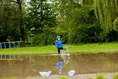 Портрет милого мальчика ребенк играя с handmade кораблем мальчик детского сада плавая шлюпка игрушки краем вод в парке стоковая фотография rf
