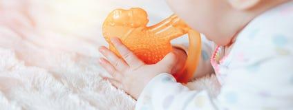 Портрет милого младенца, мальчика или девушки 6 месяцев старого, играя с игрушкой teething стоковые изображения rf
