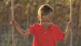 Портрет милого ребенка на качании на заходе солнца акции видеоматериалы