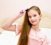 Портрет милого усмехаясь ребенка маленькой девочки чистя ее волосы щеткой стоковые изображения rf
