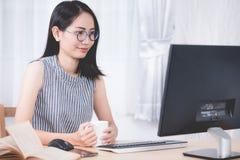 Портрет милой азиатской женщины используя компьютер peronal Стоковое Изображение RF