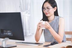 Портрет милой азиатской женщины используя компьютер peronal Стоковая Фотография