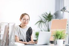 Портрет милой азиатской женщины используя компьютер peronal Стоковые Изображения