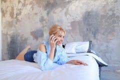 Портрет милой девушки, которая беседующ на сотовом телефоне и усмехаться, Стоковое Изображение