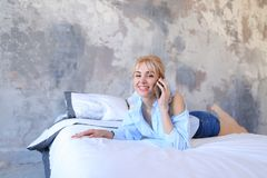 Портрет милой девушки, которая беседующ на сотовом телефоне и усмехаться, Стоковое фото RF