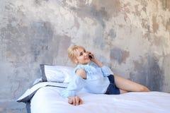 Портрет милой девушки, которая беседующ на сотовом телефоне и усмехаться, Стоковые Фото