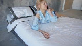 Портрет милой девушки, которая беседующ на сотовом телефоне и усмехаться, Стоковая Фотография