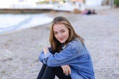 Портрет милой девушки которая усмехается и смотрится камеру, сидя дальше Стоковое Фото