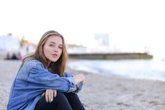Портрет милой девушки которая усмехается и смотрится камеру, сидя дальше Стоковые Фотографии RF
