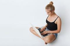 Портрет милой девушки при узел волос, одетый вскользь, держа ее ноги пересеченный пока сидящ на белом поле, читая electroni Стоковые Фото