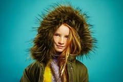 Портрет милой девушки ребенка носит стильную куртку с клобуком на голубой предпосылке стоковое фото rf
