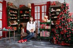 Портрет милой девушки сидит на стуле около рождественской елки дома Стоковое Фото