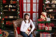 Портрет милой девушки сидит на стуле около рождественской елки дома Стоковое Изображение