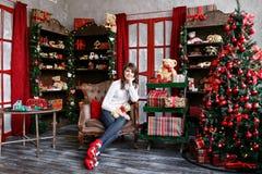 Портрет милой девушки сидит на стуле около рождественской елки дома Стоковое Изображение RF