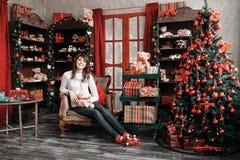 Портрет милой девушки сидит на стуле около рождественской елки дома Стоковые Изображения