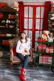 Портрет милой девушки сидит на стуле около рождественской елки дома Стоковая Фотография RF