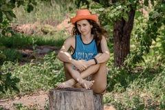 Портрет милой девушки сидя на пне Стоковые Изображения RF