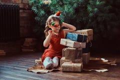 Портрет милой девушки с белокурым вьющиеся волосы нося красное платье и шляпу меньшего Санта сидя на окруженном поле стоковая фотография