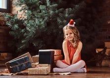 Портрет милой девушки с белокурым вьющиеся волосы нося красное платье и шляпу меньшего Санта сидя на окруженном поле стоковое изображение