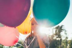 Портрет милой девушки усмехаясь показывающ зубы окруженные colorf Стоковое фото RF