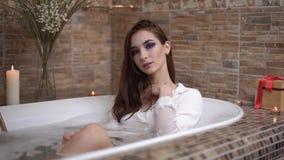 Портрет милой женщины в белой рубашке принимая ванну с пеной представляя на камере Подачи воды от водопроводного крана мило видеоматериал
