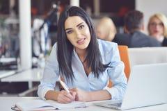 Портрет милой коммерсантки работая в офисе и взглядах занятых пока делающ примечание на тетради Стоковые Фото