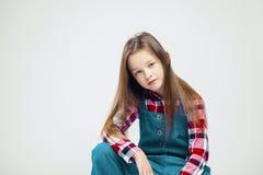 Портрет милой маленькой девочки в джинсах и рубашке шотландки фотография моды студии стоковые фотографии rf