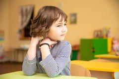 Портрет милой маленькой девочки сидя при руки сжиманные на столе в классе стоковая фотография rf