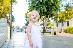 Портрет милой маленькой эмоциональной blondy девушки малыша в белый играть платья и заразительные пузыри мыла во время прогулки в Стоковое Фото