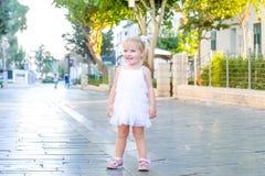 Портрет милой маленькой эмоциональной blondy девушки малыша в белый играть платья и заразительные пузыри мыла во время прогулки в Стоковое Изображение