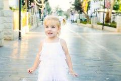 Портрет милой маленькой эмоциональной blondy девушки малыша в белый играть платья и заразительные пузыри мыла во время прогулки в Стоковые Изображения