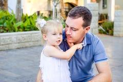 Портрет милой маленькой blondy девушки малыша в белом платье обнимая ее отца и говоря ему что-то во время прогулки в PA города Стоковые Изображения RF