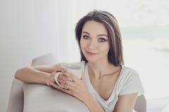 Портрет милой молодой женщины сидя на кресле и выпивая cof Стоковое Изображение RF