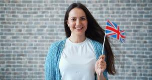 Портрет милой молодой женщины с великобританским флагом на предпосылке кирпичной стены видеоматериал