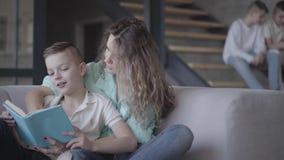 Портрет милой молодой книги чтения матери с ее сыном сидя на софе пока ее 2 предназначенных для подростков дет сидя на акции видеоматериалы