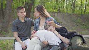 Портрет милой молодой матери с молодыми прелестными детьми отдыхая в парке r видеоматериал