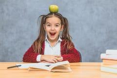 Портрет милой умной девушки с яблоком на ее голове Сидящ от стога книг на таблице, экземпляр космоса стоковые изображения