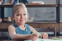 портрет милой усмехаясь девушки сидя на таблице и рисуя изображении Стоковые Изображения RF