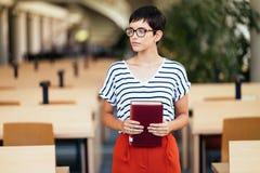 Портрет милой усмехаясь книги чтения девушки в библиотеке Стоковая Фотография