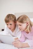 Портрет милых детей используя компьютер таблетки Стоковая Фотография RF