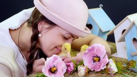 Портрет, милая молодая женщина с 2 отрезками провода и в смешной розовой шляпе играя с малыми желтыми утятами В файле видеоматериал